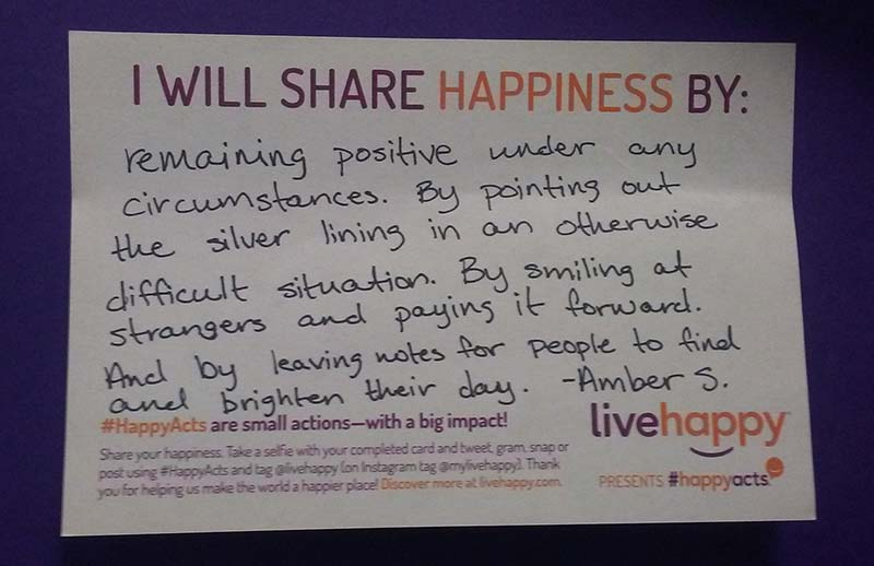 A picture of Amber S.'s note explaining how she will share happiness. It says: I will share happiness by remaining positive under any circumstances. By pointing out the silver lining in an otherwise difficult situation. By smiling at strangers and paying it forward. And by leaving notes for people to find and brighten their day.