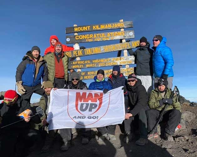 Mark Acre in front of the sign on top of Mount Kilimanjaro