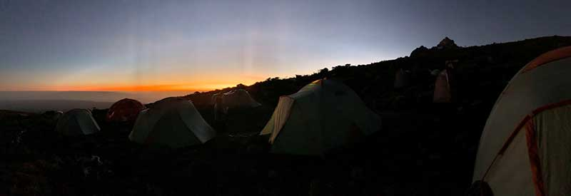 A photo of the Man Up and Go group's tents camped on the side of Mt. Kilimanjaro with a beautiful sunset in the background.
