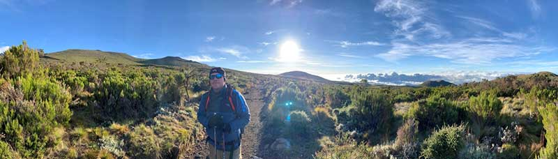 Mark Acre on his way up Kilimanjaro, standing in a landscape of grassy scrubland with a saturated blue sky in the background.