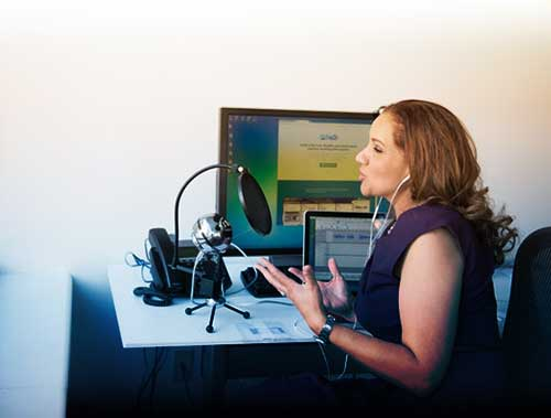 Photo of a woman sitting at a desk wearing earbuds, speaking into a USB microphone with a pop filter.