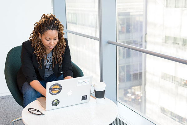 Image of a Black woman working on a laptop in an office building.